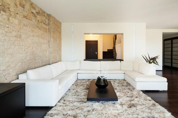 pavimento scuro, divano a forma di u bianco, grande tappeto melange e muri in pietra per interni