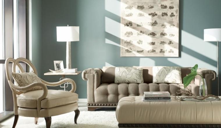 divano con cuscini tortora, parete azzurra con una stampa al centro, lampade con paralumi bianchi