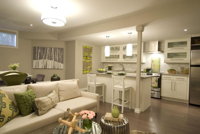 ambiente unico arredato con mobili della cucina bianchi, divano dello stesso colore e cuscini verdi