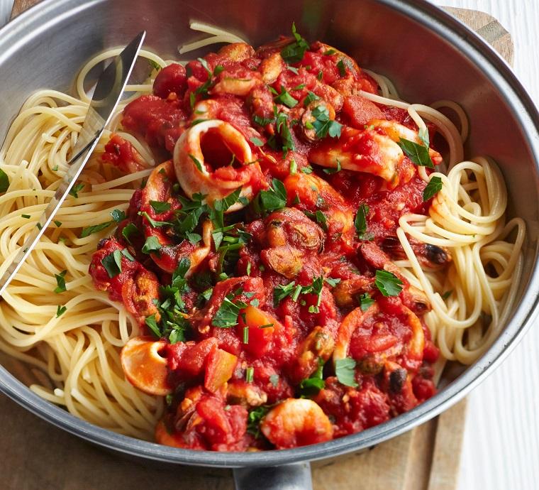 Spaghetti con sugo di pomodoro e frutti di mare in una padella di acciai inox