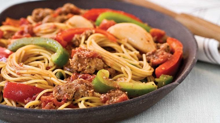 Padella con dei spaghetti al sugo di pomodoro e salsiccia, condimento con peperoni verdi e rossi
