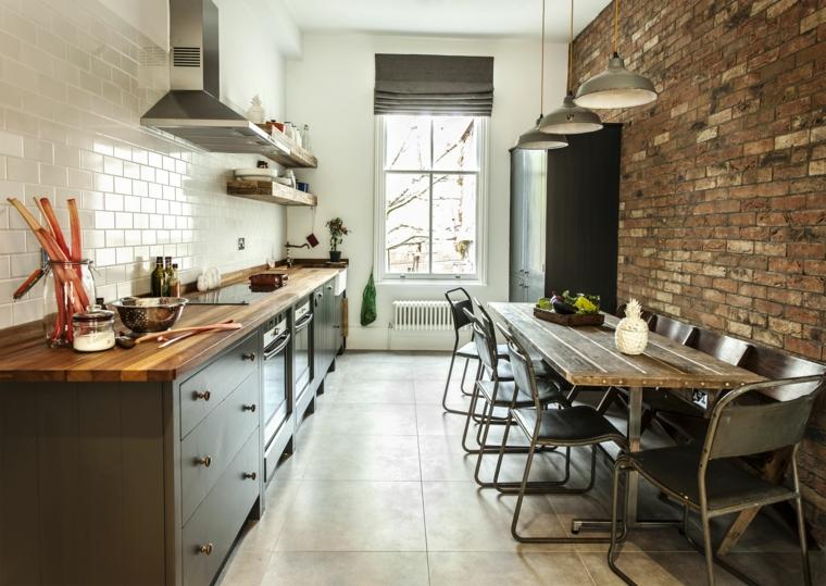 mobili della cucina scuri con top in legno, tavolo rettangolare lungo e rivestimento parete pietra