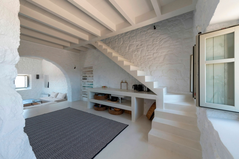 salotto dall'architettura mediterranea, con pavimento bianco e parete in muratura