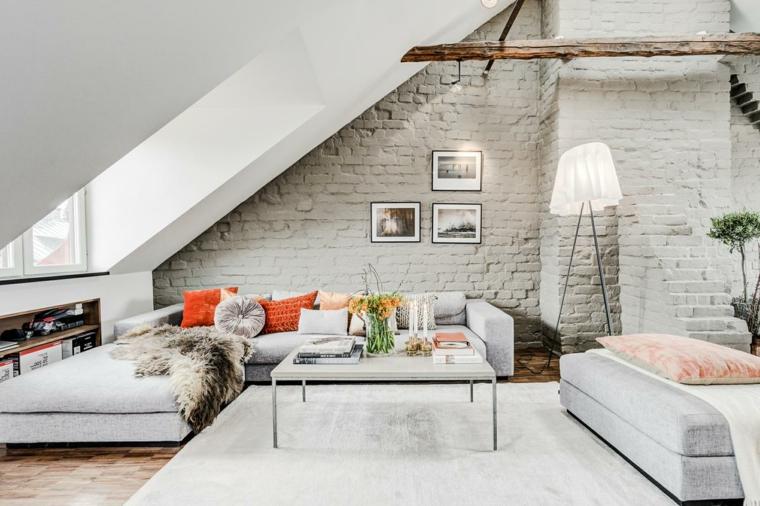 arredamento in stile scandinavo con grandi divani grigio chiaro, parete con mattoni a vista e quadri, idee mansarda