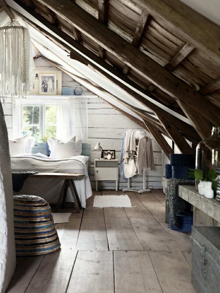 arredamento rustico in una camera da letto mansardata con pavimento in legno, finestra piccola con tende bianche