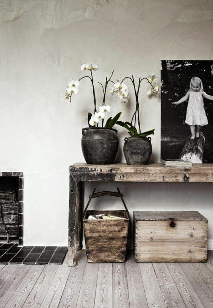 Tavolo di legno rustico con due vasi e orchidee, decorazione con una foto grande bianco e nero di una bimba