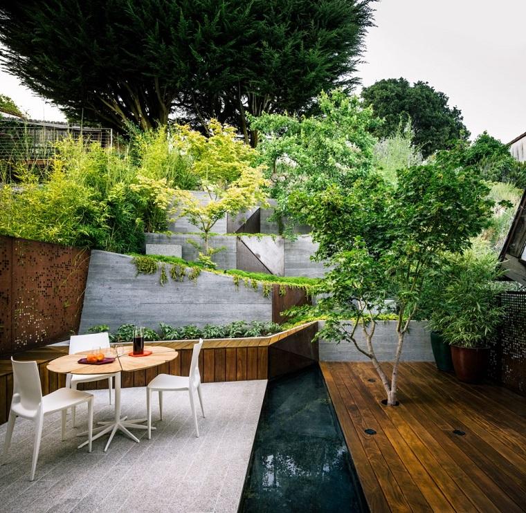 Piante da giardino fiorite, arredamento con un tavolo in legno e sedie bianche in plastica