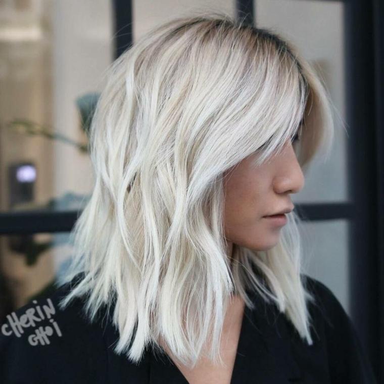 Tagli scalati medi per dei capelli di colore biondo ghiaccio con frangia separata