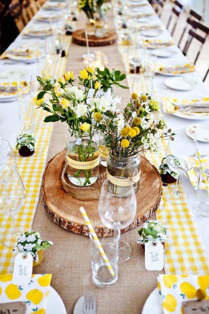 Centrotavola con rondella di legno, barattoli di vetro, vasi di fiori