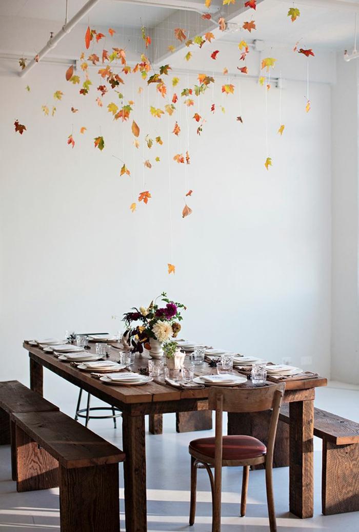 Foglie autunnali sospese, tavolo di legno, centrotavola con fiori