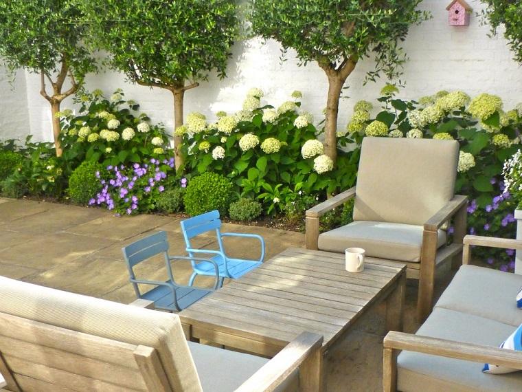 Giardino piccolo con un arredamento di legno con tavolino basso e sedie