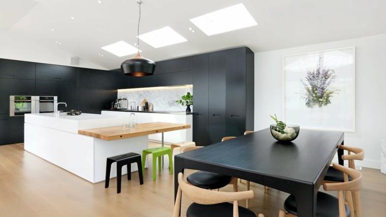 open space con cucina moderna con una grande isola e tavolo per il pranzo