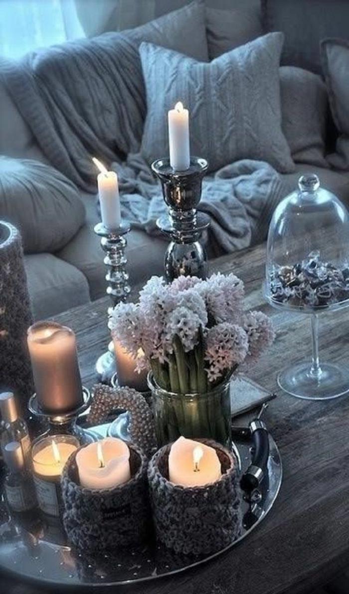 Decorare il tavolino del soggiorno con candele e fiori