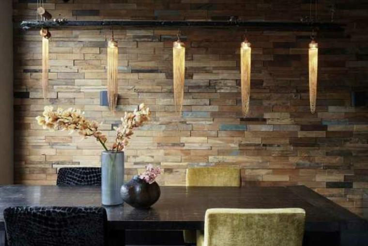 esempio di pareti rivestite in pietra colorata, tavolo in legno e vasi con dei fiori