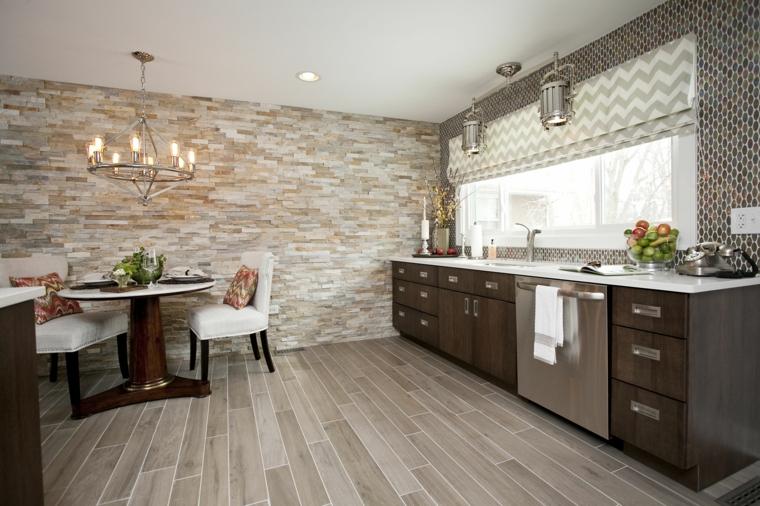 zona pranzo e cucina in un unico ambiente con pavimento in parquet e parete in pietra