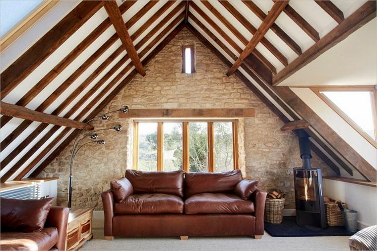 divani in pelle marrone, camino. parete con mattoni a vista, soffitto con travi in legno, mansarda arredata in stile classico