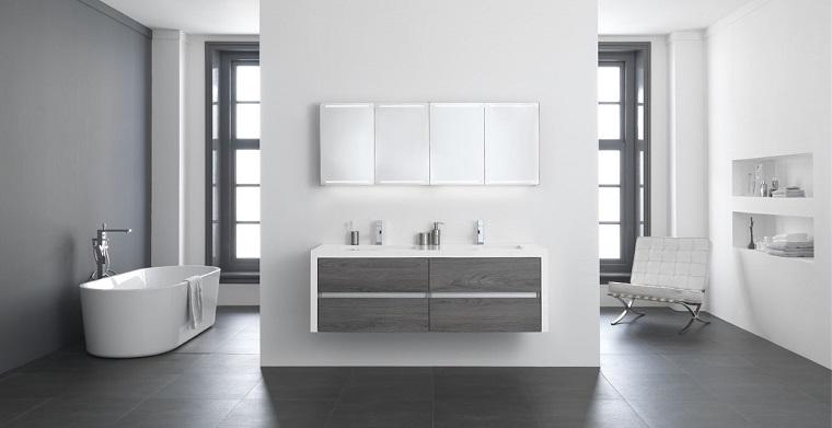 Arredare il bagno con una vasca freestanding e mobile di legno sospeso, decorazione con accessori in nicchie sulla parete
