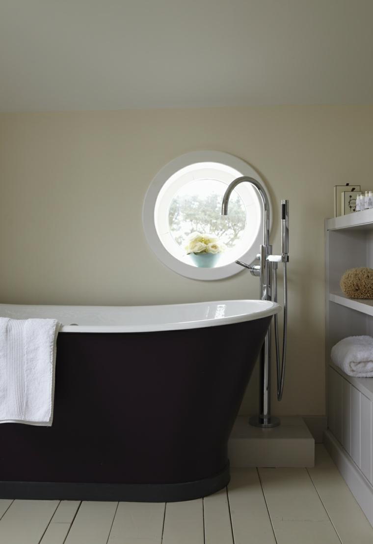 bagno con pavimento in legno chiaro, vasca dal design retrò e muri chiari tortora