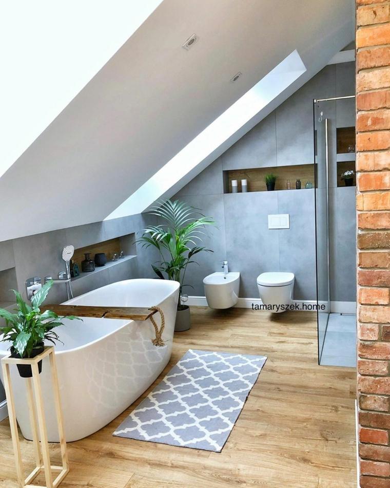 Sala da bagno con soffitto in pendenza, bagno con vasca freestanding vicino ad un tappeto