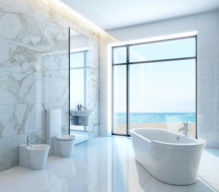 Idee bagno moderno piccolo con vasca e sanitari di colore bianco, grande finestra con vista sul mare