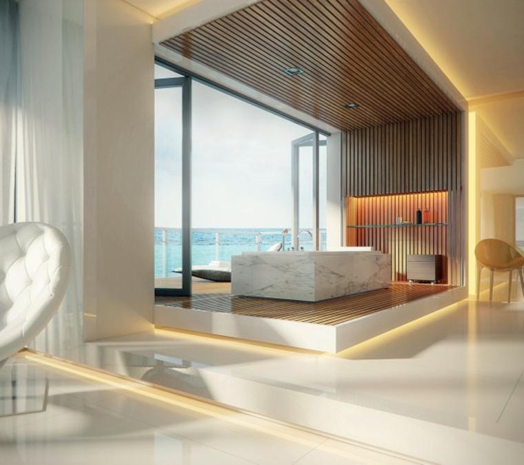 Rivestimenti bagni esempi con marmo, vasca bassa su una superficie di legno e faretti sul soffitto