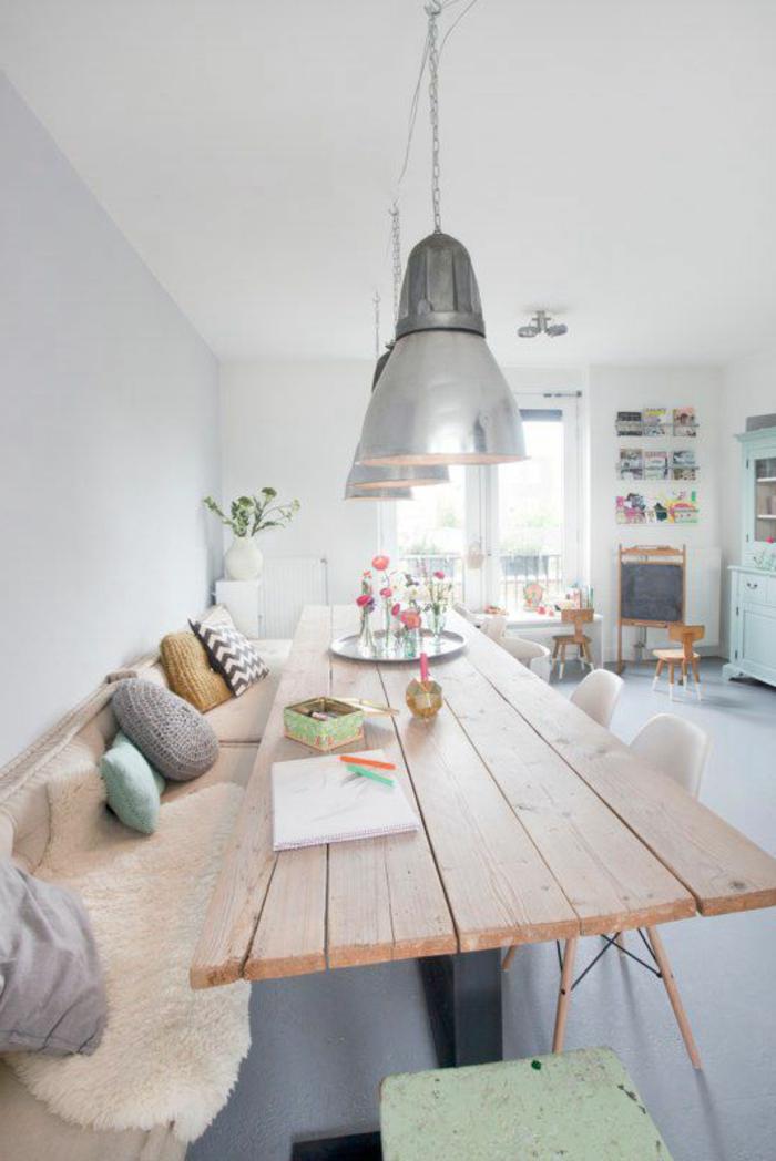 Tavolo lungo di legno, centrotavola con fiori, divano con cuscini