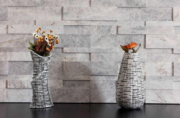 esempio di muri in pietra per interni color ghiaccio, due vasi dalla forma allungata con fiori