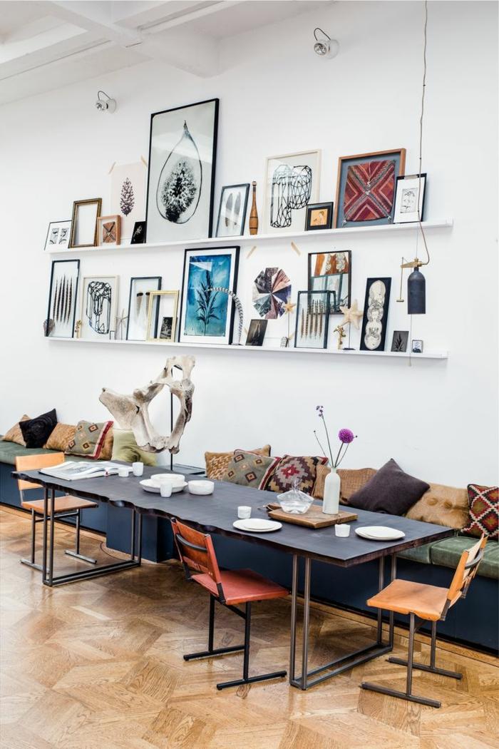 Tavole apparecchiate originali e decorare con vasi di fiori, parete con mensole e quadri