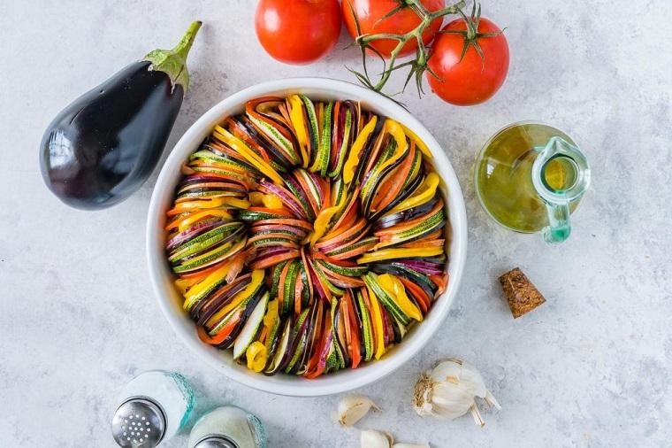 Teglia rotonda con verdure tagliate a rondelle, ratatouille e secondi piatti semplici e gustosi