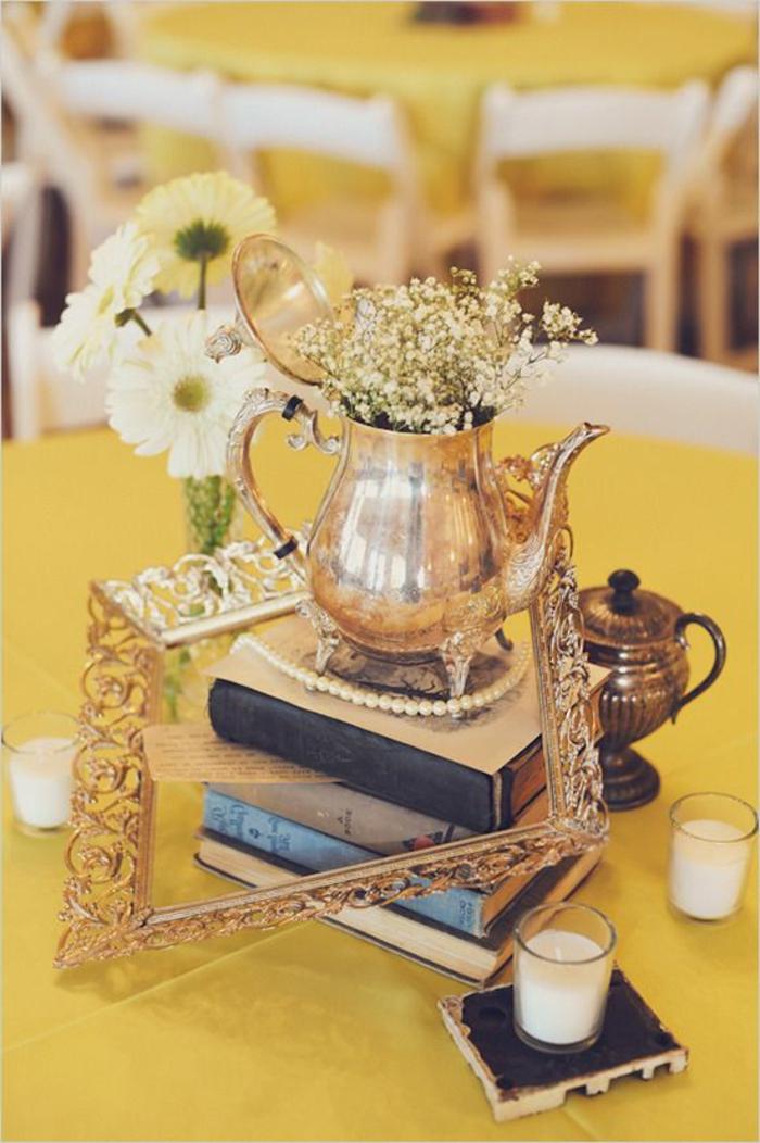 Tavola apparecchiata in modo originale con libri e candele, cornice in oro con bigliettino
