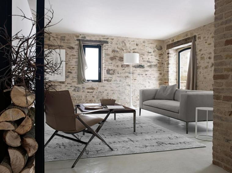 salotto dallo stile nordico con divano grigio, poltrona marrone in pelle, lampada bianca e rivestimento parete in pietra