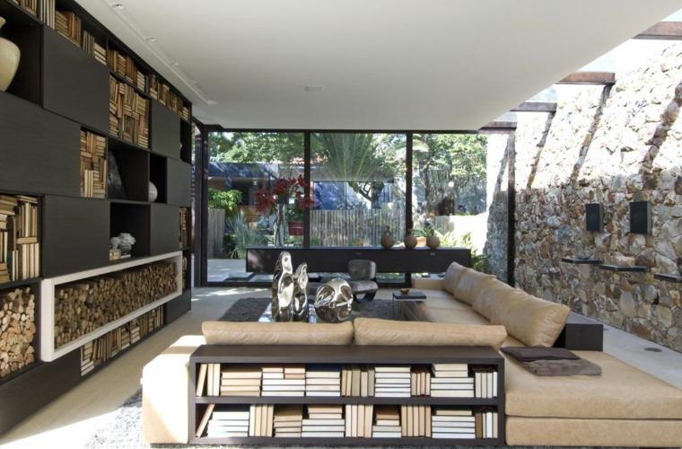 originale soggiorno con un grande divano, marrone chiaro, una parete vetrata e un rivestimento parete in pietra