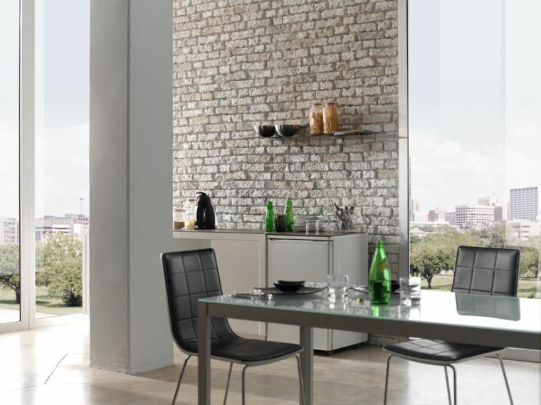 ampia e luminosa zona pranzo con tavolo e sedie in pelle nera, mobile bianco e parete rivestita in pietra