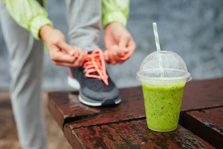 Bere i frullati di frutta per dimagrire mentre si fa sport, smoothie in contenitore di plastica