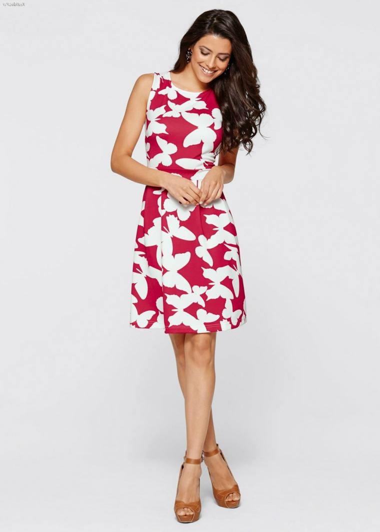 Donna con un vestito corto di colore rosso decorato con farfalle di colore bianco