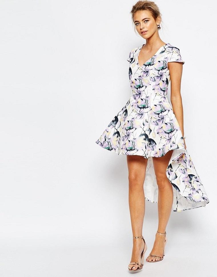 Donna con un abito elegante da cerimonia dal tagli asimmetrico lungo dietro e stampe floreali