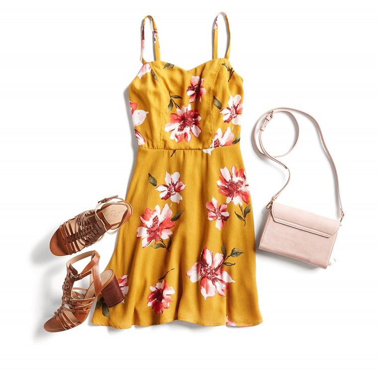 Vestito corto di colore giallo con stampe motivi floreali in abbinamento con scarpe e borsa
