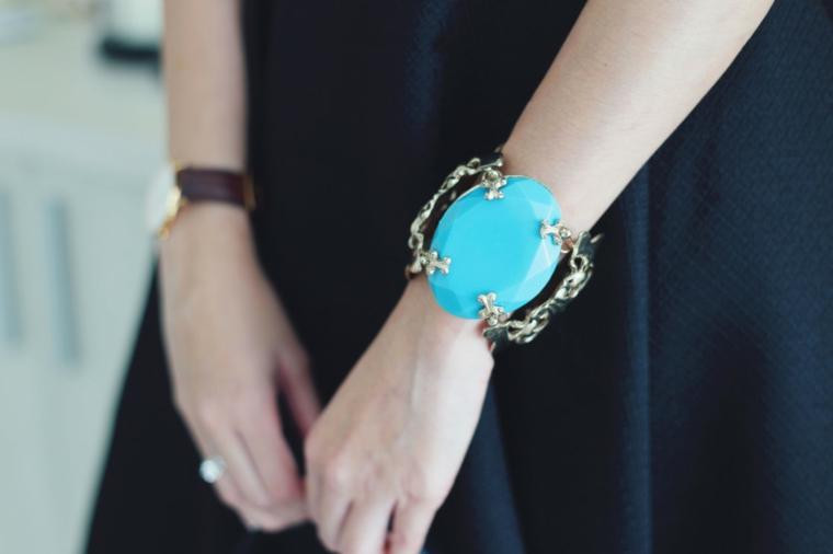 Bracciale di colore azzurro con struttura metallica come accessorio di un abbigliamento elegante per matrimonio