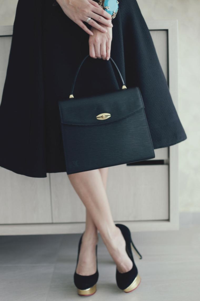 Parte inferiore di un vestito nero a ruota, borsa a mano in pelle abbinata alle scarpe alte