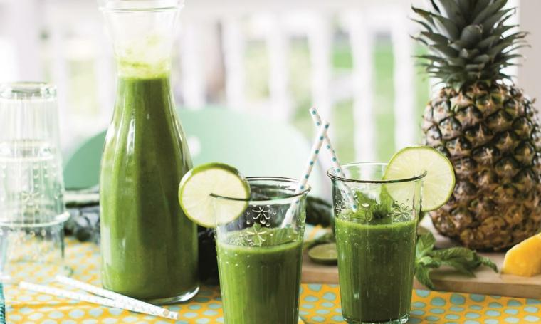 Smoothie in bottiglia di vetro con ananas e foglie di menta. bicchiere decorato con lime