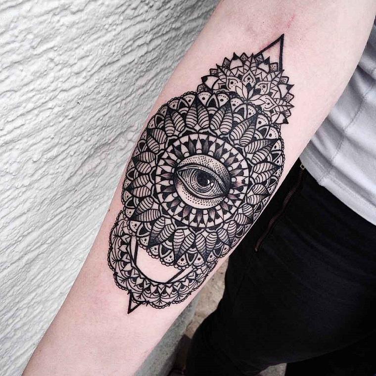 Fiore di loto tattoo sul braccio di una donna, disegno con ornamenti e occhio interiore