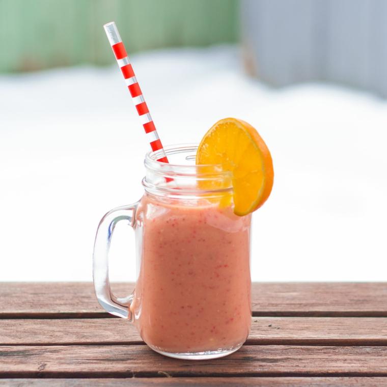 Colazione detox con un frullato di fragola e fetta di arancia come decorazione