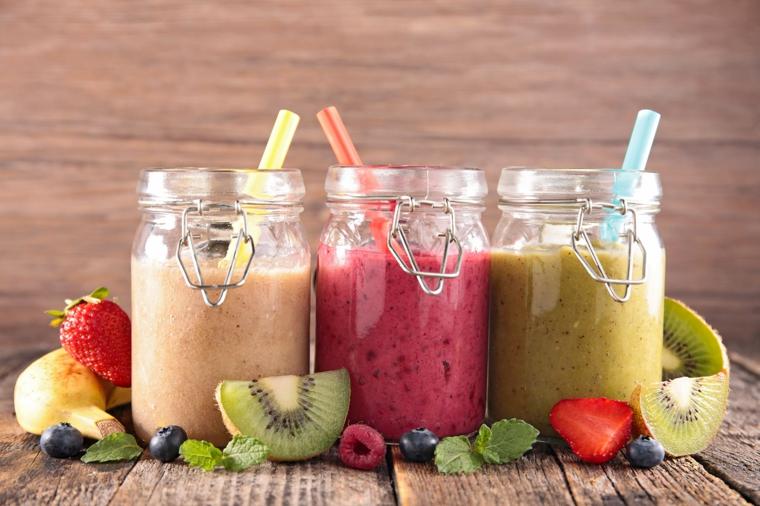 Frullati detox di frutta di stagione serviti in barattoli di vetro con cannucce