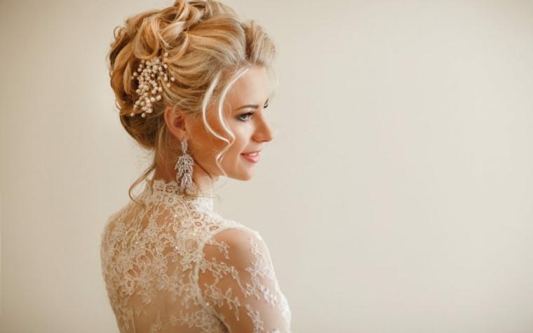elegante acconciatura raccolta con un fermaglio di perle, trucco e parrucco sposa