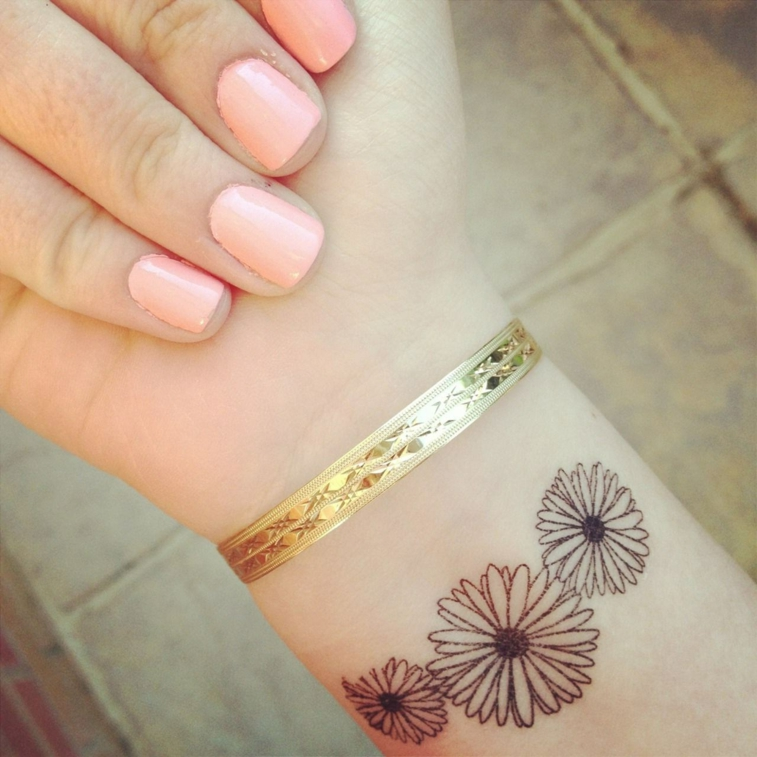 tre margherite di varie dimensioni, disegni ideali per tatuaggi al polso femminili
