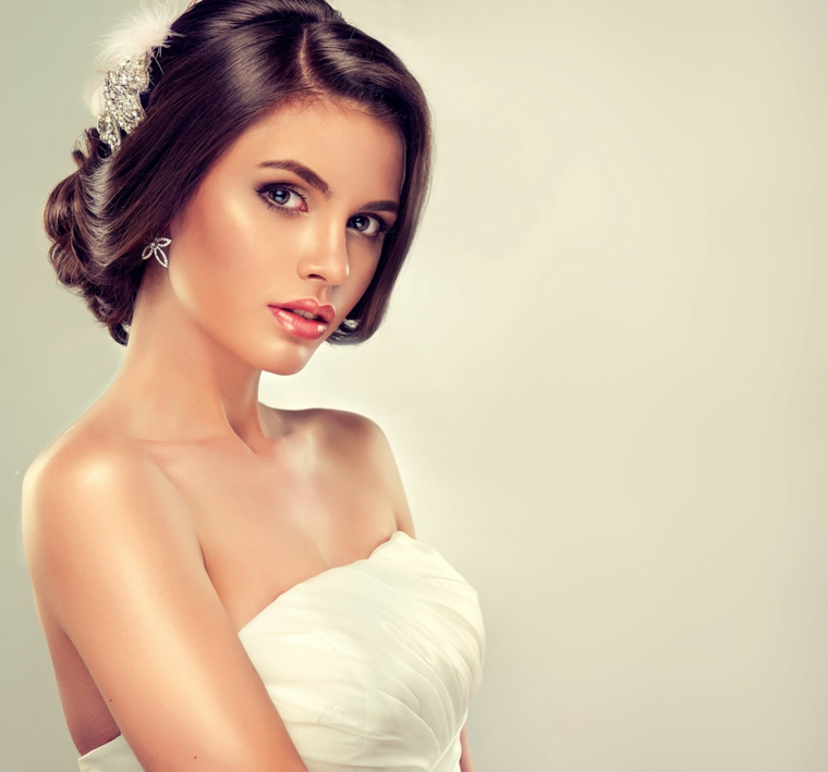 splendida ragazza con capelli castani raccolti con un fermaglio di brillanti, rossetto lucido arancio, un maquillage duraturo