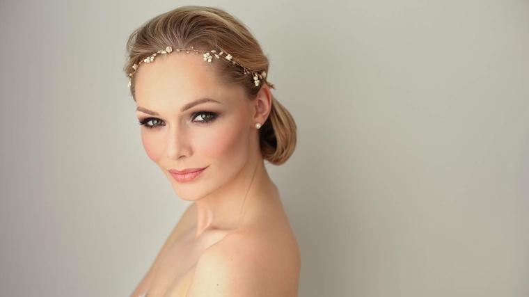 sofisticato look per una sposa con i capelli biondi raccolti, rossetto albicocca e fard rosa antico