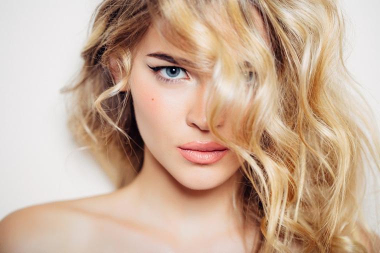 capelli biondi con delle morbide onde, occhi azzurri e neo sulla guancia, come fare i capelli mossi