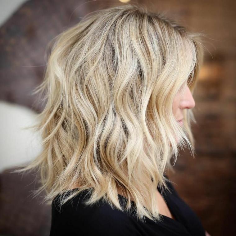 bellissimo esempio di capelli biondo platino con un taglio scalato di media lunghezza