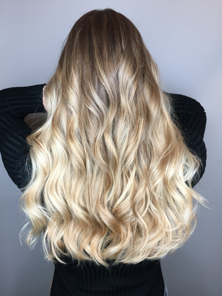 splendidi capelli lunghi pari con una piega ondulata balayage capelli biondi